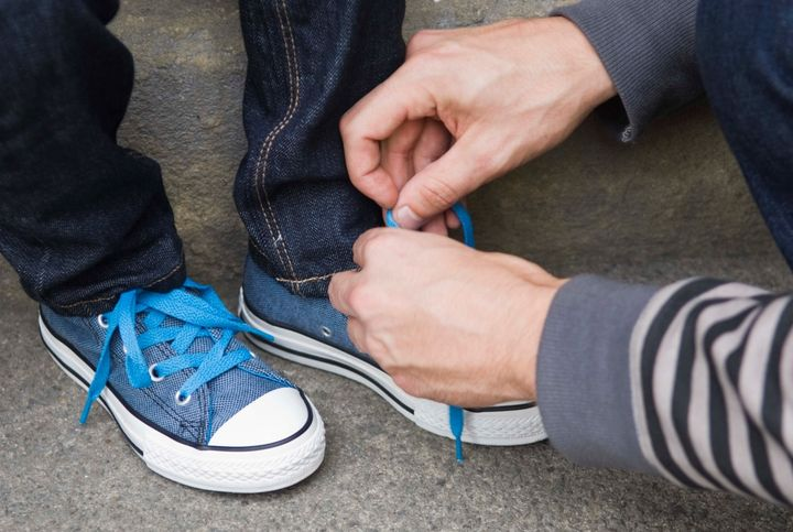Adult tying shoes of child